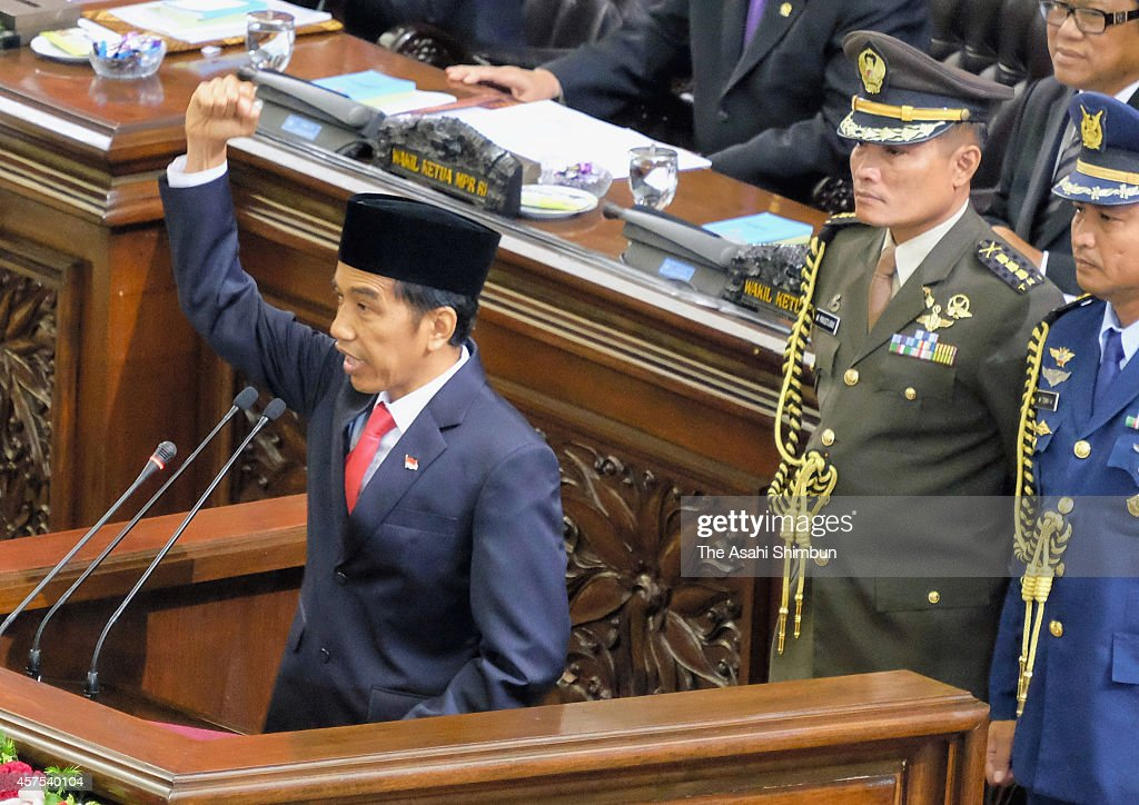 President Joko Widodo raises his fist after his first speech during his inauguration ceremony at the House of Representative building on October 20, 2014 in Jakarta, Indonesia. Joko Widodo is today sworn in as the president of Indonesia with an inauguration ceremony held in Jakarta. Widodo was the eventual winner of a tightly fought and sometimes controversial election race against opposition candidate Prabowo Subianto.