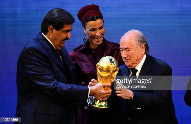 President Josef Blatter hands over the World Cup trophy to the Emir of the State of Qatar Sheikh Hamad bin Khalifa AlThani and his wife Chair of...