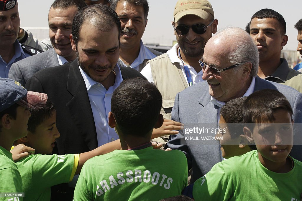 President, Joseph Blatter (R) and FIFA Vice-President Prince Ali bin al-Hussein from Jordan talk with children during a visit at the northern Jordanian Zaatari refugee camp on July 6, 2013 in Mafraq near the border with Syria. Blatter is on a four-day-official visit to Jordan, Palestinian territories and Israel during which he will notably launch football turf fields. AFP/PHOTO/KHALIL MAZRAAWI