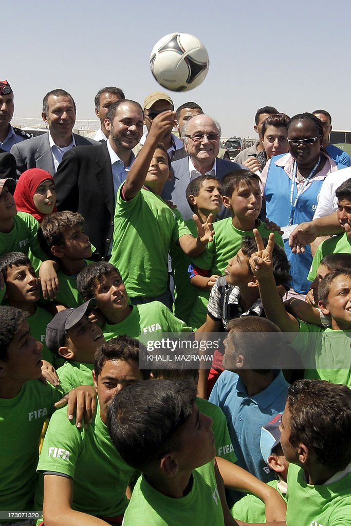 President, Joseph Blatter (C-top) and FIFA Vice-President Prince Ali bin al-Hussein from Jordan (top-2ndL) talk with children during a visit at the northern Jordanian Zaatari refugee camp on July 6, 2013 in Mafraq near the border with Syria. Blatter is on a four-day-official visit to Jordan, Palestinian territories and Israel during which he will notably launch football turf fields. AFP/PHOTO/KHALIL MAZRAAWI