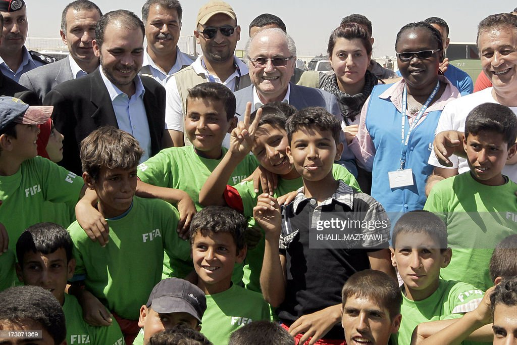 President, Joseph Blatter (C) and FIFA Vice-President Prince Ali bin al-Hussein from Jordan (L-top) pose with children during a visit at the northern Jordanian Zaatari refugee camp on July 6, 2013 in Mafraq near the border with Syria. Blatter is on a four-day-official visit to Jordan, Palestinian territories and Israel during which he will notably launch football turf fields. AFP/PHOTO/KHALIL MAZRAAWI