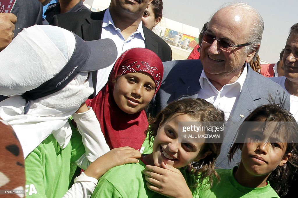 President, Joseph Blatter poses with children during a visit at the northern Jordanian Zaatari refugee camp on July 6, 2013 in Mafraq near the border with Syria. Blatter is on a four-day-official visit to Jordan, Palestinian territories and Israel during which he will notably launch football turf fields. AFP/PHOTO/KHALIL MAZRAAWI