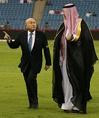 President Joseph Blatter speaks with a Saudi offical as he walks on the pitch prior to the opening match of the 22nd Gulf Cup football tournament...