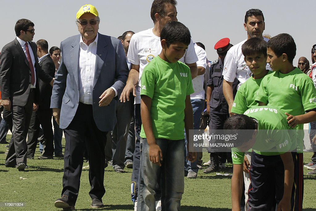 President, Joseph Blatter (2ndL) walks past children during a visit at the northern Jordanian Zaatari refugee camp on July 6, 2013 in Mafraq near the border with Syria. Blatter is on a four-day-official visit to Jordan, Palestinian territories and Israel during which he will notably launch football turf fields. AFP/PHOTO/KHALIL MAZRAAWI
