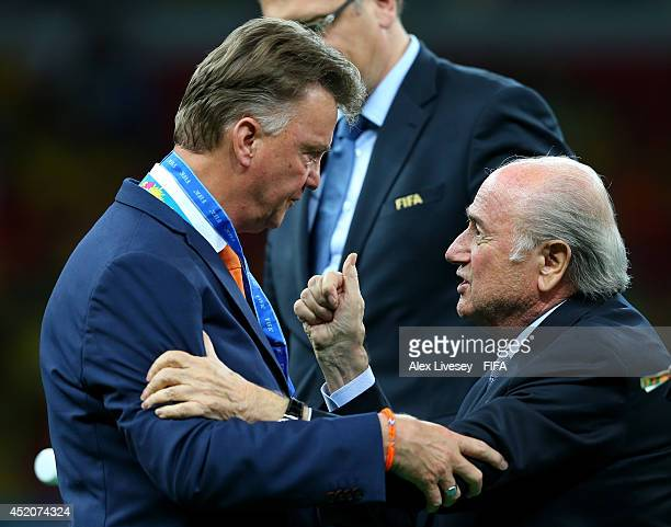 President Joseph S Blatter congratulates head coach Louis van Gaal of the Netherlands during the medal ceremony after the 2014 FIFA World Cup Brazil...