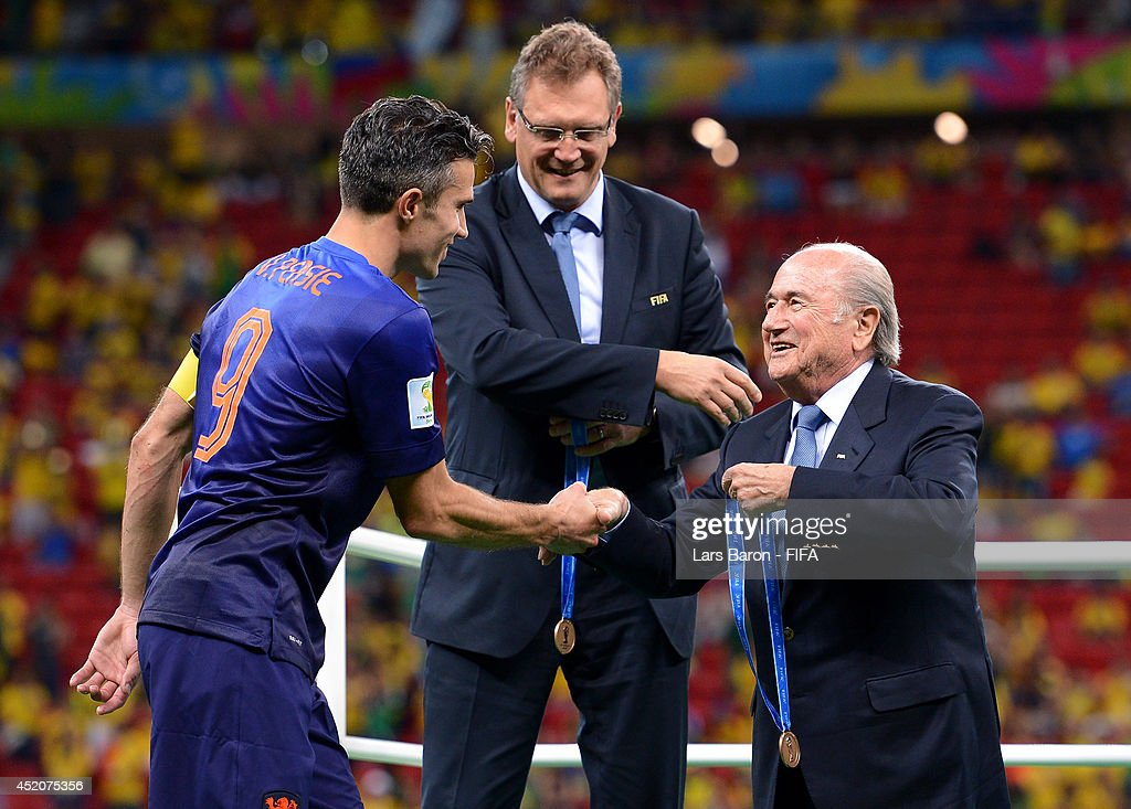 President Joseph S. Blatter congratulates Robin van Persie of the Netherlands during the medal ceremony after the 2014 FIFA World Cup Brazil 3rd Place Playoff match between Brazil and Netherlands at Estadio Nacional on July 12, 2014 in Brasilia, Brazil.