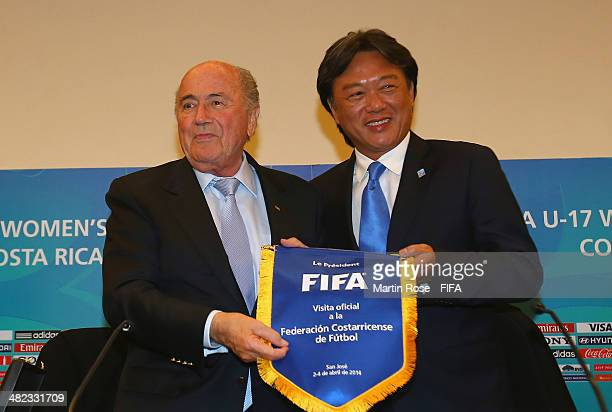 President Joseph S Blatter hands over a FIFA pennant to LOC president Eduardo Li during a FIFA U17 Women's World Cup press conference at...