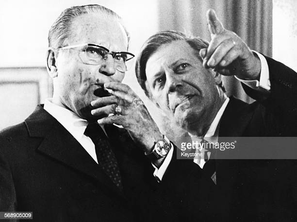 President Josip Broz Tito of Yugoslavia smoking a cigar as he talks with West German Chancellor Helmut Schmidt during an official visit to Germany...
