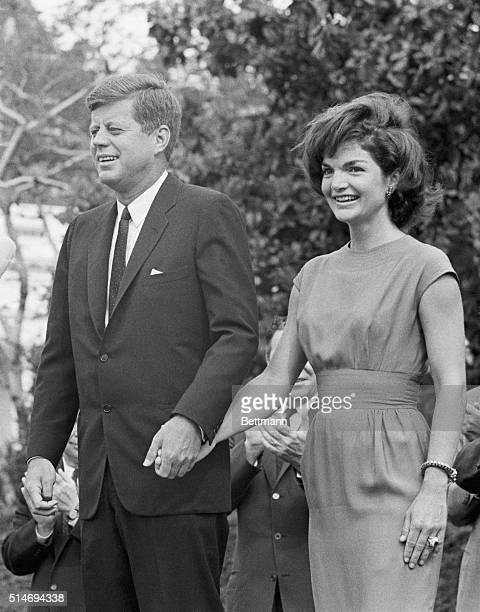 President Kennedy and the First Lady hold hands as they meet with delegates to the 1962 Conference for Democratic Women