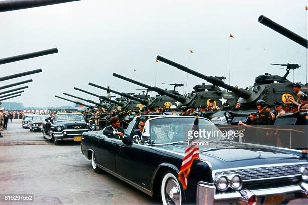 President Kennedy rides in a convertible past tanks and soldiers as he inspects the troops at Fuegerhorst Kaserne Hanau West Germany