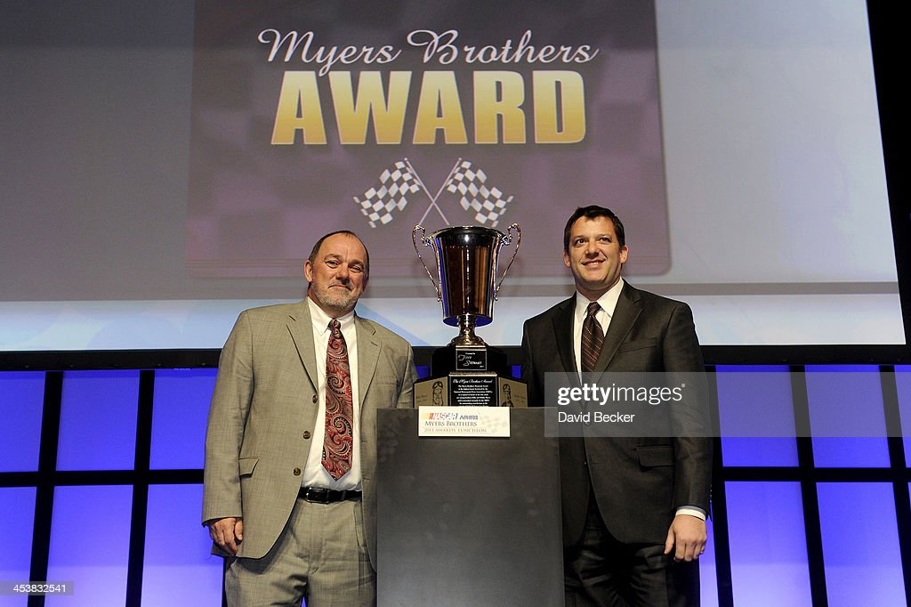 President Kenny Bruce and NASCAR Sprint Cup Series driver <a gi-track='captionPersonalityLinkClicked' href=/galleries/search?phrase=Tony+Stewart+-+Race+Car+Driver&family=editorial&specificpeople=201686 ng-click='$event.stopPropagation()'>Tony Stewart</a> pose after Stewart wins the Myers Brother Award at the NMPA Myers Brothers Awards Luncheon at the Encore Las Vegas on December 5, 2013 in Las Vegas, Nevada.