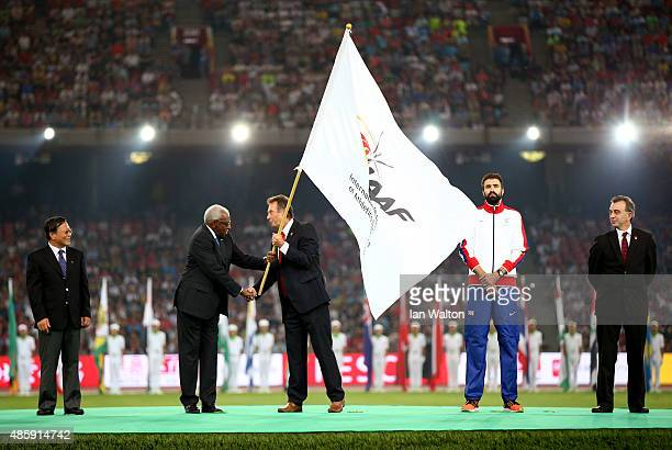 President Lamine Diack hands over the IAAF flag to President of UK athletics Lynn Davies during the closing ceremony during day nine of the 15th IAAF...