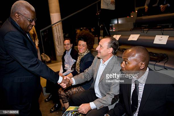President Lamine Diack shakes hands with former spanish athlete Fermin Cacho during the IAAF Centenary Exhibition Open Ceremony at the Joan Antoni...