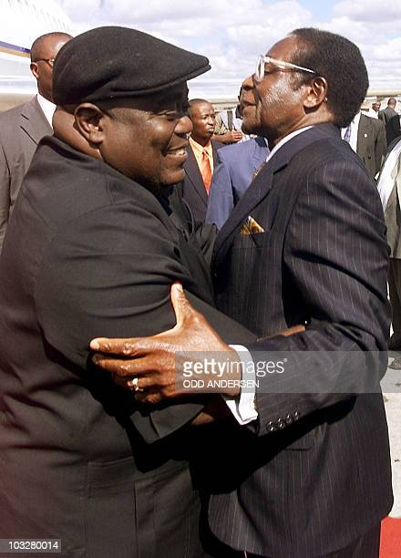 President Laurent Kabila of the Democratic Republic of Congo embraces Zimbabwean counterpart Robert Mugabe upon his arrival at Harare international...