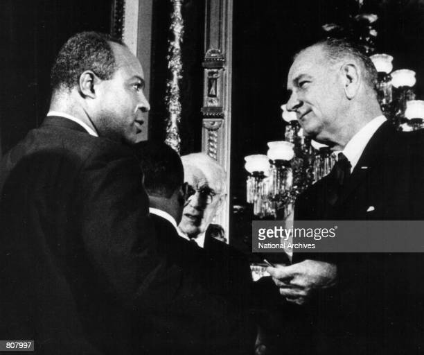 President Lyndon B Johnson presents one of the pens used to sign the Voting Rights Act of 1965 to James Farmer Director of the Congress of Racial...
