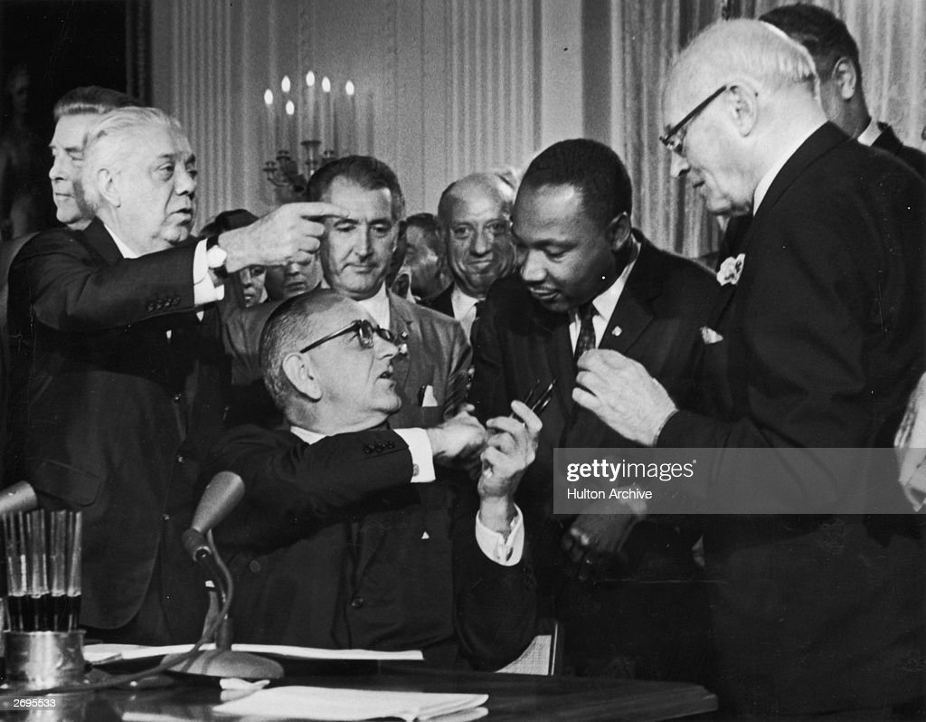 US President Lyndon B. Johnson shakes the hand of Dr. Martin Luther King Jr. (1929 - 1968) at the signing of the Civil Rights Act while officials look on, Washington DC.