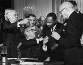 US President Lyndon B Johnson shakes the hand of Dr Martin Luther King Jr at the signing of the Civil Rights Act while officials look on Washington DC