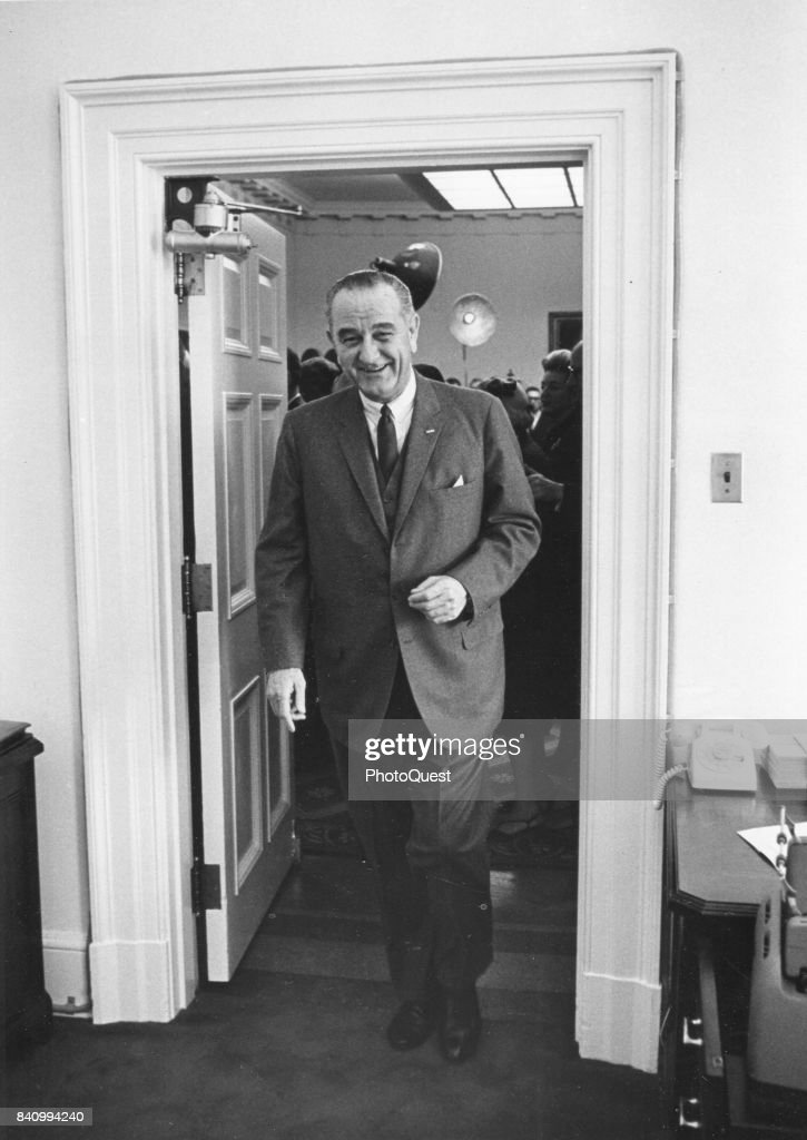 US President Lyndon B Johnson (1908- 1973) smiles as he through a White House doorway after a press conference, Washington DC, 1964.