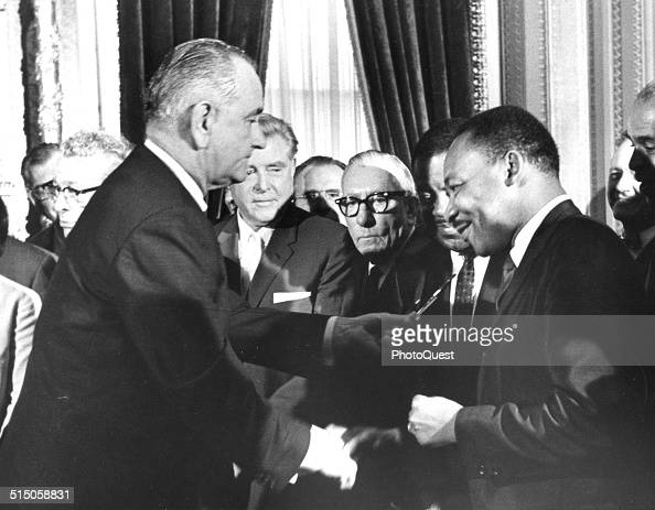 President Lyndon Johnson hands a souvenir pen to the Reverend Martin Luther King Jr after signing the Voting Rights Bill at the US Capital Washington...