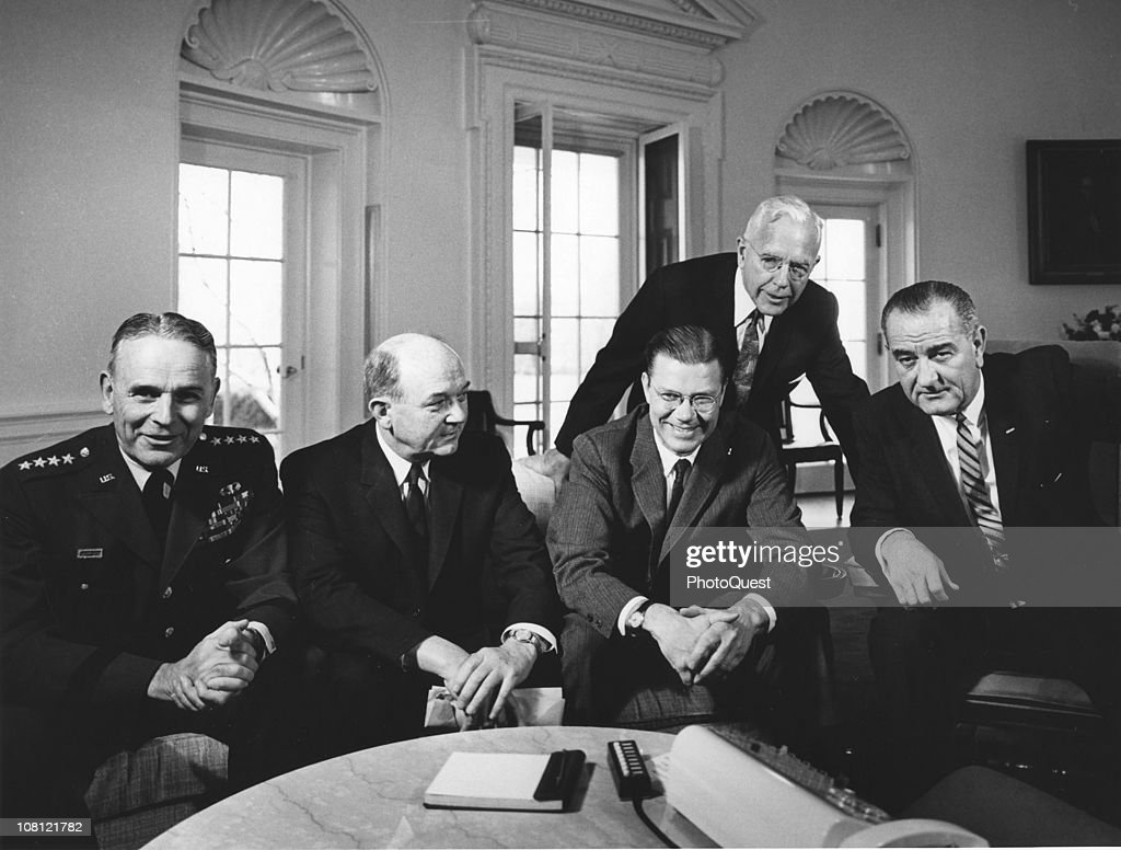 US President <a gi-track='captionPersonalityLinkClicked' href=/galleries/search?phrase=Lyndon+Johnson&family=editorial&specificpeople=91450 ng-click='$event.stopPropagation()'>Lyndon Johnson</a> (1908 - 1973) (right) poses in the White House's Oval Office with Chairman of the Joint Chiefs of Staff General <a gi-track='captionPersonalityLinkClicked' href=/galleries/search?phrase=Maxwell+D.+Taylor&family=editorial&specificpeople=214213 ng-click='$event.stopPropagation()'>Maxwell D. Taylor</a> (1909 - 1994) (left), Secretary of State <a gi-track='captionPersonalityLinkClicked' href=/galleries/search?phrase=Dean+Rusk&family=editorial&specificpeople=93282 ng-click='$event.stopPropagation()'>Dean Rusk</a> (1909 - 1994) (second left), Secretary of Defense <a gi-track='captionPersonalityLinkClicked' href=/galleries/search?phrase=Robert+McNamara&family=editorial&specificpeople=94002 ng-click='$event.stopPropagation()'>Robert McNamara</a> (1916 - 2009) (center), and an unidentified man (standing), Washington DC, March 13, 1964.