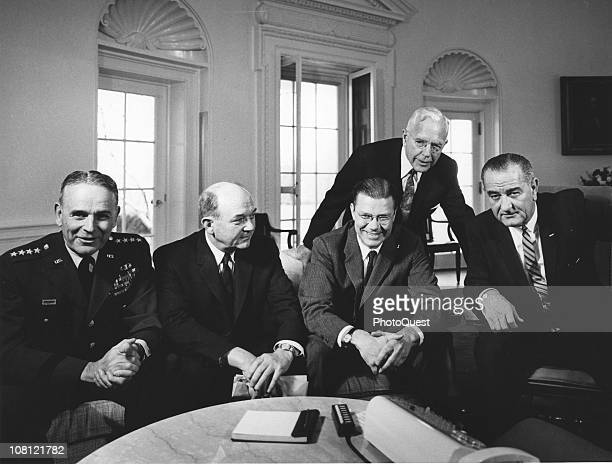US President Lyndon Johnson poses in the White House's Oval Office with Chairman of the Joint Chiefs of Staff General Maxwell D Taylor Secretary of...
