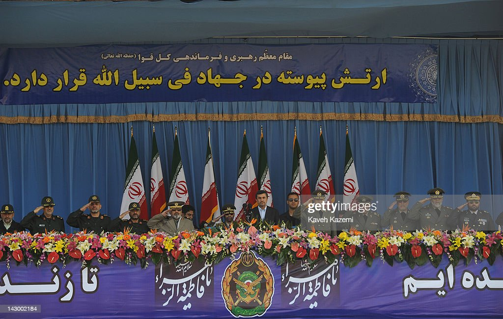 President Mahmoud Ahmadinejad stands alongside military commanders of the Iranian armed forces as they watch a parade commemorating the National Army...