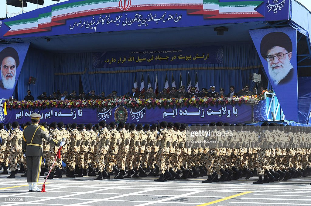 President Mahmoud Ahmadinejad stands alongside military commanders of the Iranian armed forces as they watch soldiers march during a parade...