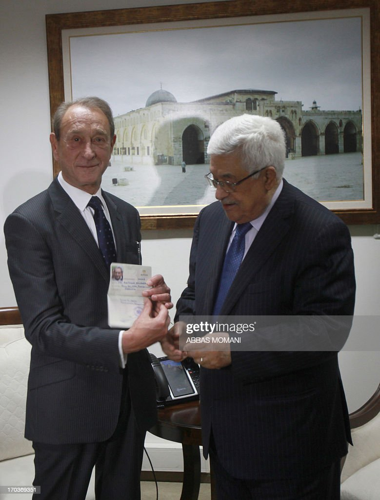 President Mahmud Abbas looks on as the Mayor of Paris, Bertrand Delanoë (L), shows off his honorary Palestinian citizenship during his visit to the West Bank city of Ramallah on June 12, 2013. AFP PHOTO/ABBAS MOMANI