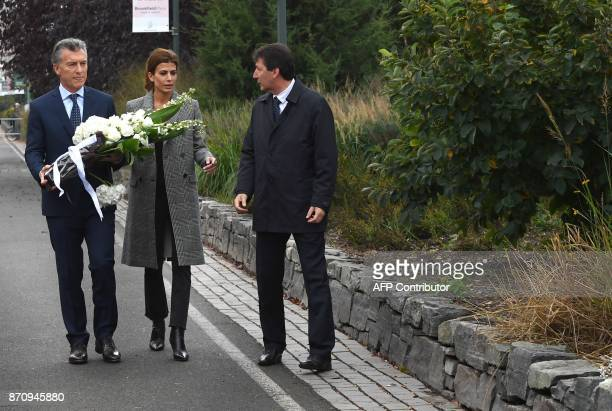 President Mauricio Macri of Argentina along with the First Lady of Argentina Juliana Awada hold flowers as they attend a tribute to victims of the...
