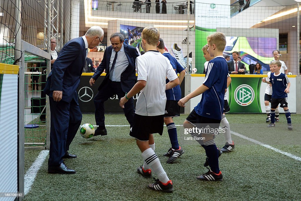 UEFA president <a gi-track='captionPersonalityLinkClicked' href=/galleries/search?phrase=Michel+Platini&family=editorial&specificpeople=206862 ng-click='$event.stopPropagation()'>Michel Platini</a> (C) and former German national player <a gi-track='captionPersonalityLinkClicked' href=/galleries/search?phrase=Franz+Beckenbauer&family=editorial&specificpeople=210545 ng-click='$event.stopPropagation()'>Franz Beckenbauer</a> (L) play football with children prior to the DFB Bundestag at the NCC Nuremberg on October 24, 2013 in Nuremberg, Germany.