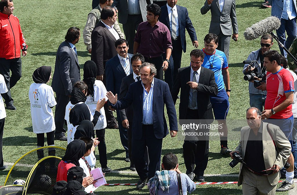 UEFA president Michel Platini (C) greets Afghan teenage footballers as he arrives at Kabul Stadium on September 22, 2013. UEFA president Michel Platini visits Afghanistan to lend his support to football in the war-torn country, weeks after it claimed its first international trophy. Afghanistan erupted in celebration after the national team beat India 2-0 in the final of the South Asian Football Federation championship on September 11. AFP PHOTO/Massoud HOSSAINI