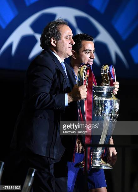 President Michel Platini holds the trophy before giving it to Xavi Hernandez of Barcelona during the UEFA Champions League Final between Juventus and...