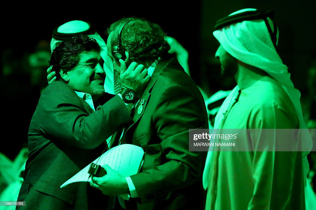 UEFA president Michel Platini (C) hugs Argentinian football icon and former player Diego Maradona (L) during the first session of the International Sports Conference in Dubai on December 28, 2012.