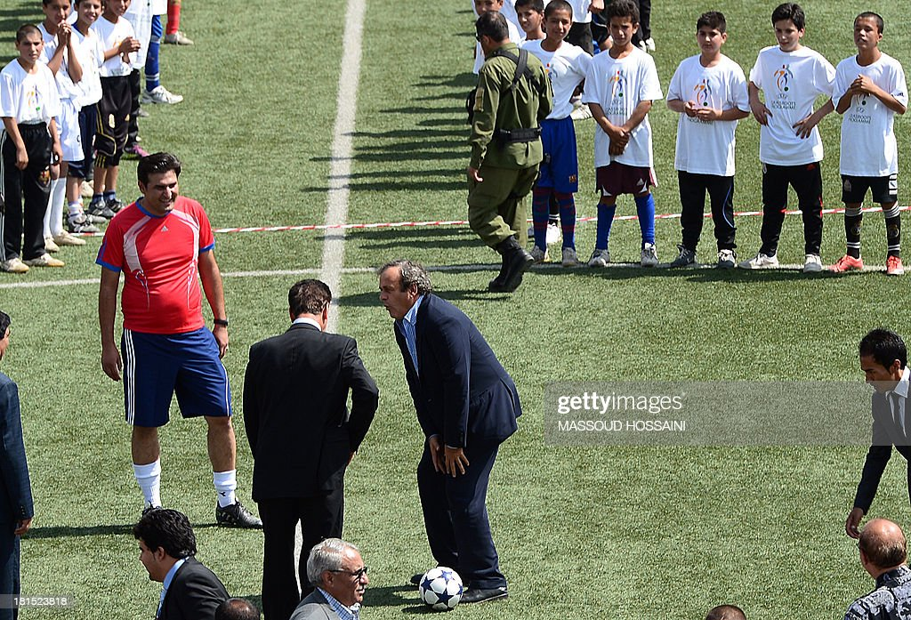 UEFA president Michel Platini (C) passes the ball to Afghan teenage footballers on his arrival at Kabul Stadium on September 22, 2013. UEFA president Michel Platini visits Afghanistan to lend his support to football in the war-torn country, weeks after it claimed its first international trophy. Afghanistan erupted in celebration after the national team beat India 2-0 in the final of the South Asian Football Federation championship on September 11. AFP PHOTO/Massoud HOSSAINI