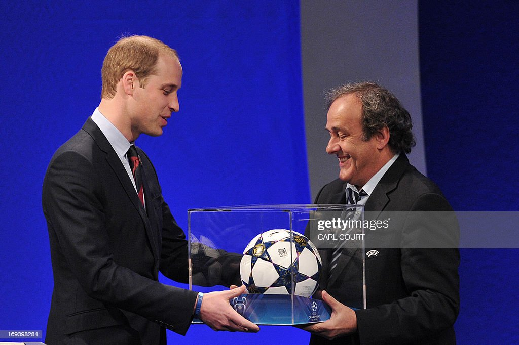 President Michel Platini (R) presents Britain's Prince William, the Duke of Cambridge with a football during the UEFA Congress in central London on May 24, 2013. Speaking at the UEFA congress UEFA President Michel Platini identified the three main problems facing the game as match-fixing, discrimination and financial excesses.