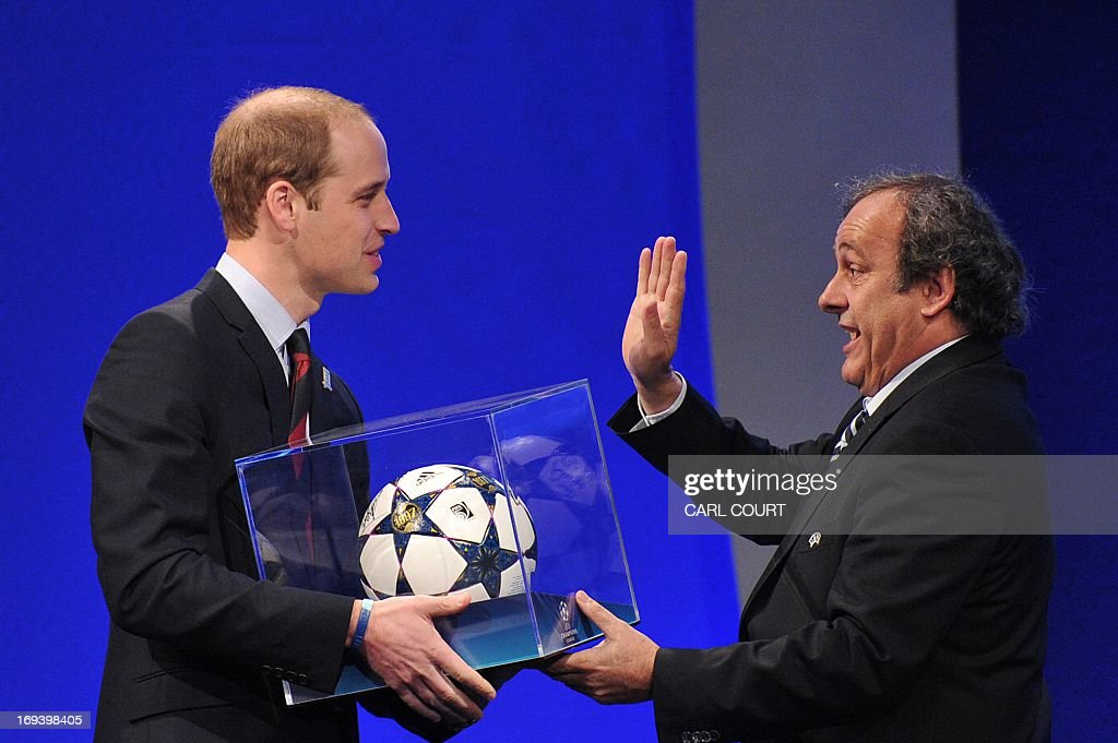 President Michel Platini (R) presents Britain's Prince William, the Duke of Cambridge with a football during the UEFA Congress in central London on May 24, 2013. Speaking at the UEFA congress UEFA President Michel Platini identified the three main problems facing the game as match-fixing, discrimination and financial excesses. AFP PHOTO/CARL COURT