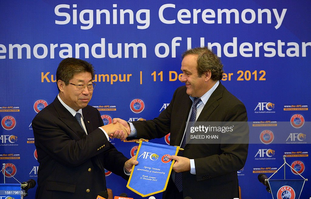 UEFA president Michel Platini (R) receives an AFC flag from acting President Zhang Jilong (L) during a memorandum of understanding signing ceremony between the two football confederations in Bukit Jalil outside Kuala Lumpur on December 11, 2012. AFP PHOTO / Saeed Khan