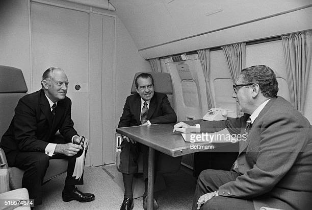 President Nixon confers with Secy of State Rogers and Dr Henry Kissinger national security affairs adviser aboard Air Force One enroute to the...