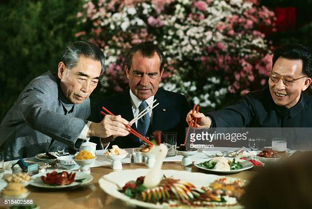 President Nixon holds his chopsticks in the ready position as Premier Chou Enlai and Shanghai Communist Party leader Chang Chunchiao reach in front...