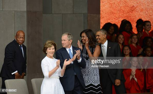 President Obama accompanied by first lady Michelle Obama former president George Bush and former first lady Laura Bush smile at Congressman John...