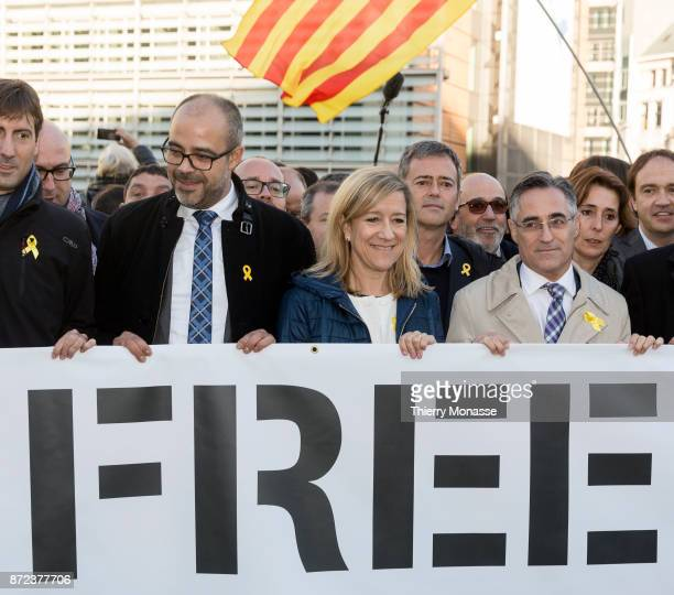 President of AMI Neus Lloveras lines up with Catalan proindependence mayors holding a banner as they demonstrate in support of detained officials in...