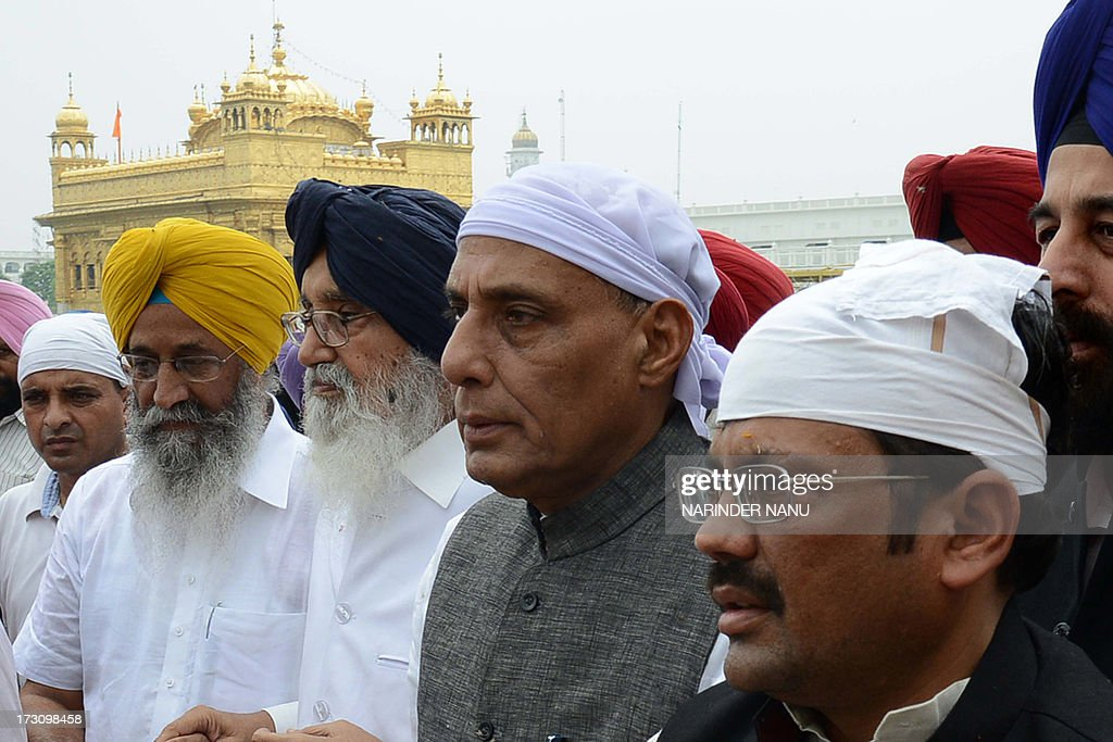 President of Bharatiya Janata Party (BJP), Rajnath Singh (2R), Punjab state chief minister Parkash Singh Badal (3L) and president of Punjab BJP, Kamal Sharma (R) pay their respects at the Sikh Shrine Golden temple in Amritsar on July 7, 2013. Rajnath Singh visited the city to attend a two-day meeting with the executive body of the Punjab state BJP at a resort on the outskirts of Amritsar and paid his respects at the Sikh Shrine, Jallianwala Bagh and Durgiana temple. AFP PHOTO/NARINDER NANU