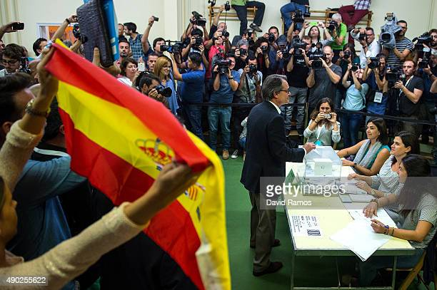President of Catalonia Artur Mas casts his vote as members of the ultraright wing Spanish political party VOX hold up spanish flags and banners at a...