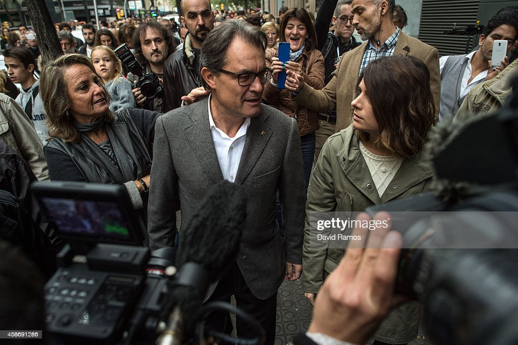 President of Catalonia Artur Mas leaves a polling station surrounded by members of the media and supporters after casting his ballot on November 9...