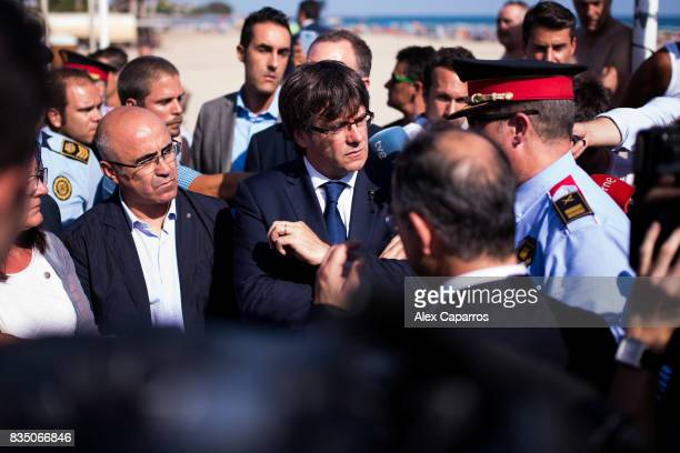President of Catalonia Carles Puigdemont speaks with a police officer as he visits the spot where five terrorists were shot by police on August 18...