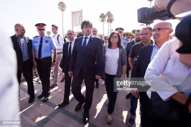 President of Catalonia Carles Puigdemont walks between Minister of the Presidency Jordi Turull and Mayor of Cambrils Cami Mendoza after visiting the...