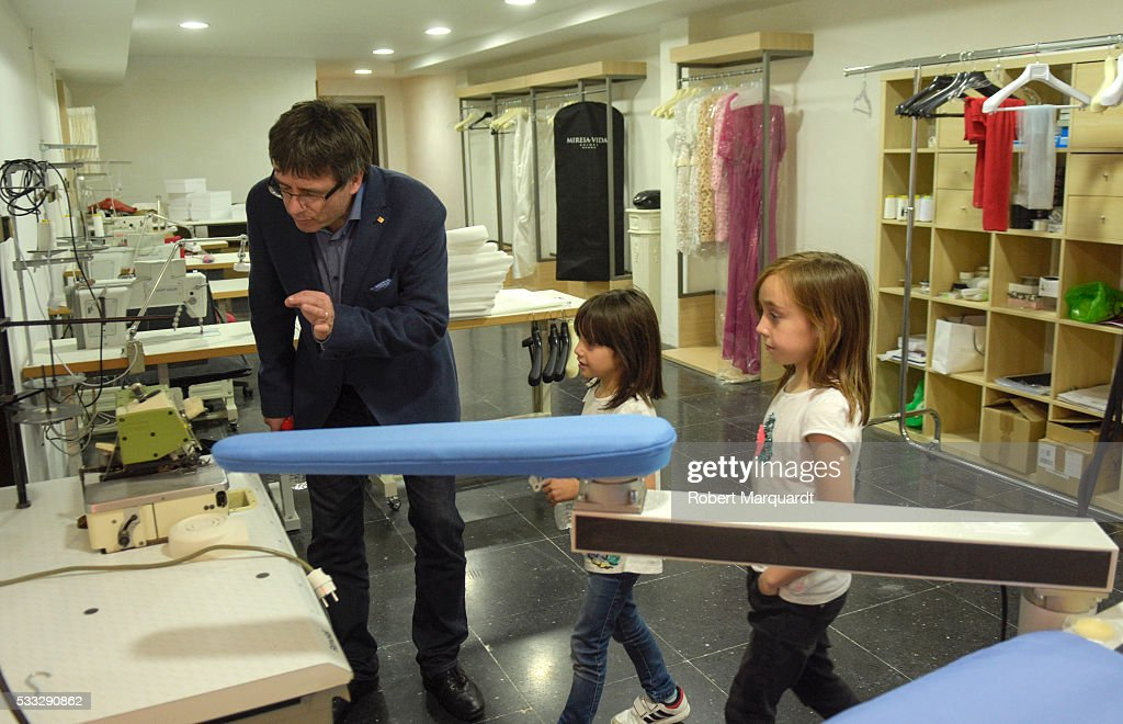 President of Catalunya Carles Puigdemont (L) visits the new store of Mireia Vidal Bridal on May 21, 2016 in Barcelona, Spain.