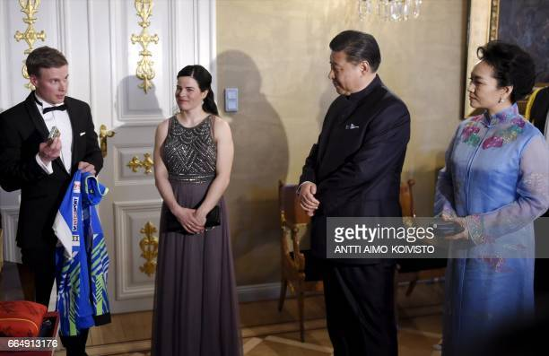President of China Xi Jinping and wife Peng Liyuan receive Finland's national team training suits from Finnish nordic skiers Matti Heikkinen and...