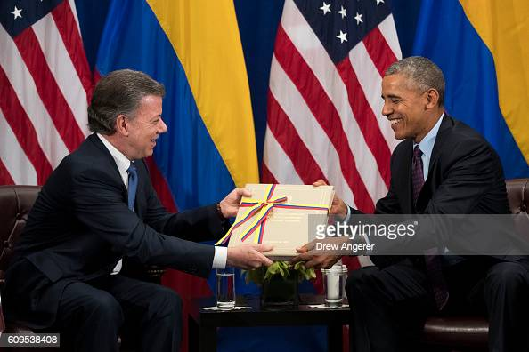 President of Colombia Juan Manuel Santos gives US President Barack Obama a copy of the Colombian peace agreement during bilateral meeting at the...