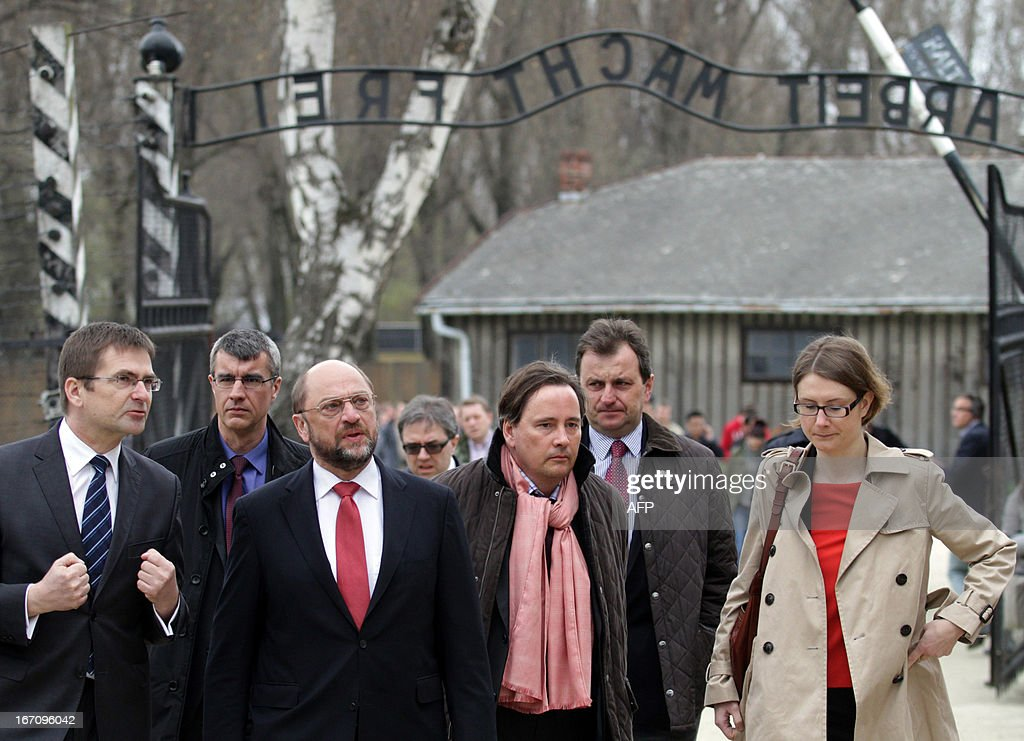 President of European Parliament Martin Schulz (3rd L) and members of his delegation pass the gate of the former Auschwitz concentration camp during their visit at the Auschwitz-Birkenau memorial site on April 20, 2013. Schulz visited the former Nazi death camp at the end of his three days visit to Poland.